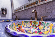 Talavera sink, colorful bathroom sink, talavera tin bathroom mirror, blue solid surface countertop, blue cross hatch vinyl wall covering, vinyl wall covering, commercial bathroom, Mexican bathroom, Mexican restaurant bathroom, floral sink, #interiordesign, #interiordesigner, #interiordecorating, #interiordecor
