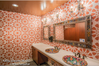 Mexican bathroom, Mexican restaurant bathroom, talavera sink, colorful sink, floral sink, drop in sinks, white solid surface countertop, commercial bathroom, large pattern wall covering, vinyl wall covering, medallion wall covering, talavera tile, talavera tile and tine mirror, crystal and iron wall sconce, wall scones, orange wall covering, orange brown ceiling, high gloss ceiling paint, #interiordesign, #interiordesigner, #interiordecorating, #interiordecor