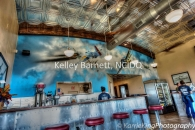 Hangar 6, Hangar 6 Air Cafe, Uvalde restaurant, Sherwin Williams paints, restaurant on air field, wood ceiling beams, curved wood ceiling beams, Karrie King Photography, metal wrap, metal wrapped bar, red leather bar stools, custom mural, custom wall mural, aerial dog fight mural, Vigini Studios, pressed tin ceiling, school house pendants, exposed AC duct, exposed ductwork,  granite bar top, red granite bar top, faux wood porcelain tile floor, wood look porcelain tile floor, #interiordesign, #interiordesigner, #interiordecorating, #interiordecor